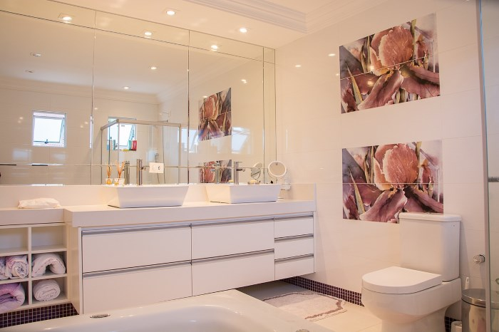 elegantno belo kupatilo sa velikim ogledalima i lampama