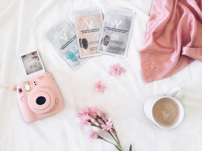 mineralne maske vichy, šolja kafe, cveće i instant foto-aparat