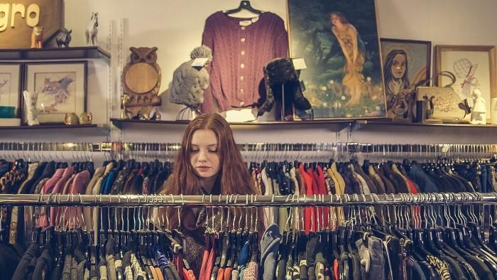 devojka između rafova sa garderobom