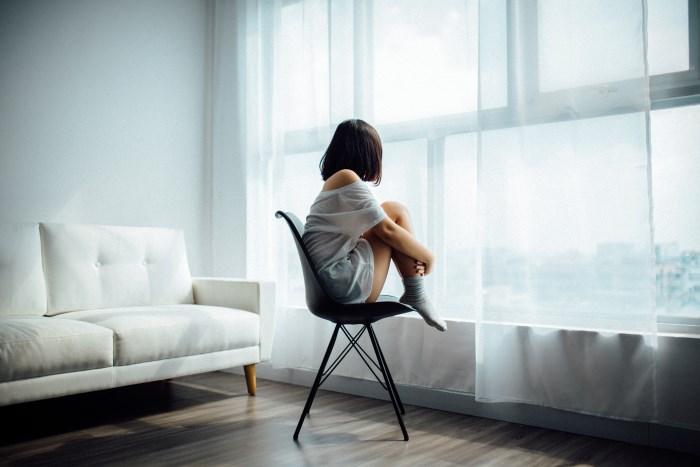tužna žena na stolici gleda kroz prozor