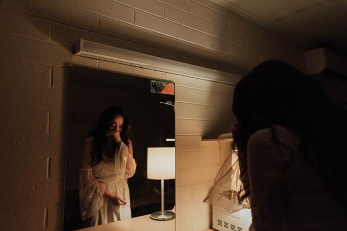 žena u beloj haljini plače pred ogledalom