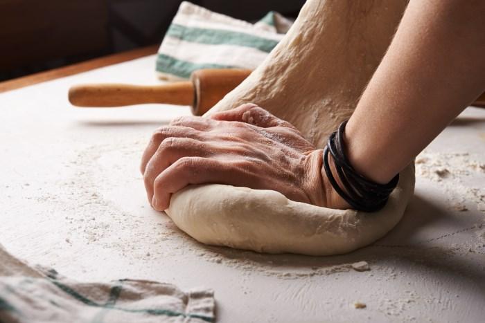 ženske ruke mese testo - slika za svetski dan hleba